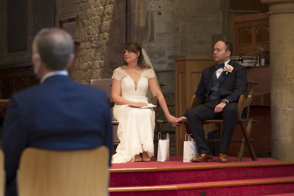 Bride and groom holding hands listening to vicar's sermon at St Stephen's Church in Tonbridge, Kent