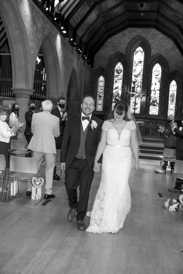 Bride and Groom laughing as guests clap in wedding ceremony at St Stephen's Church in Tonbridge, Kent