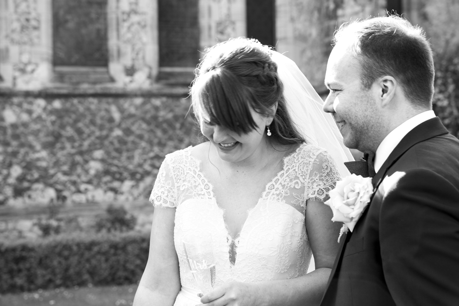 Bride and Groom laughing drinking champagne at St Stephen's Church in Tonbridge, Kent