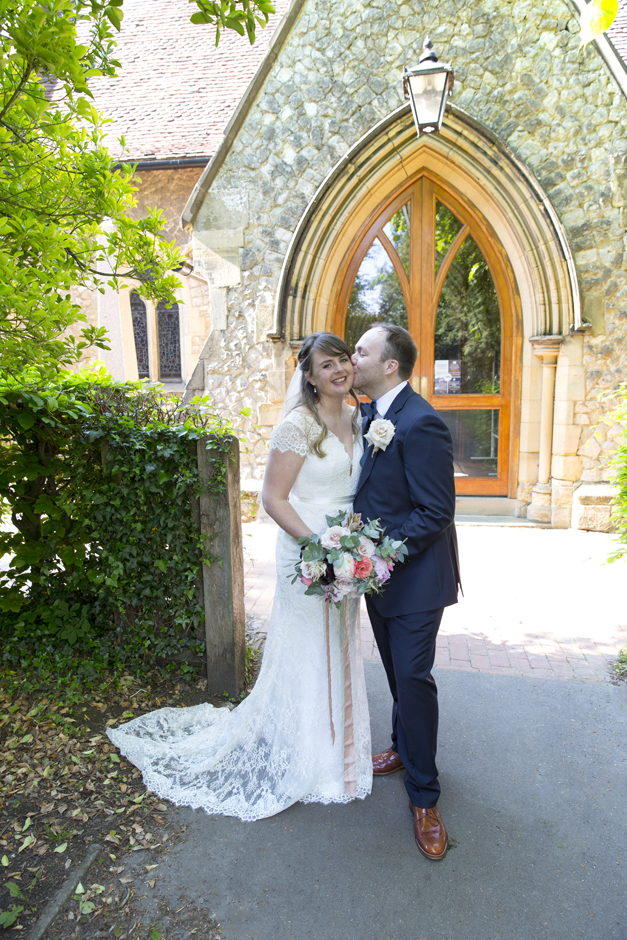 Bride and Groom portrait with groom kissing bride outside St Stephen's Church in Tonbridge, Kent