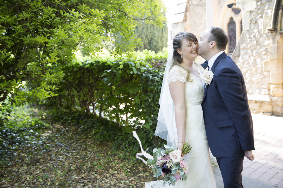 Bride laughing being kissed by groom in wedding portrait outside of St Stephen's Church in Tonbridge, Kent