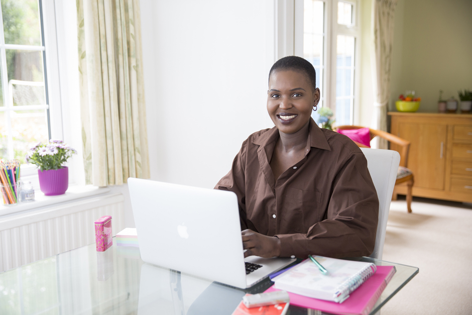 Black business woman at desk on laptop captured by Kent wedding photographer Victoria Green
