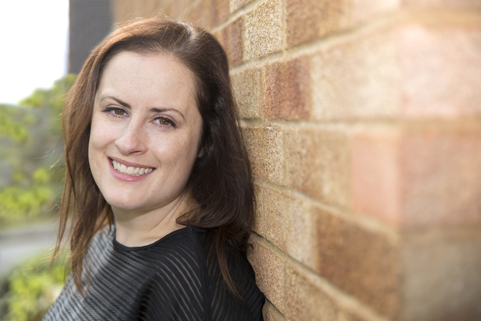 Business woman head shot with faded brick background captured by Kent photographer Victoria Green