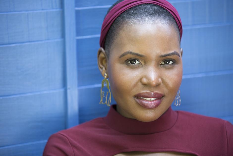 Black woman head portrait against striking blue background captured by Kent photographer Victoria Green