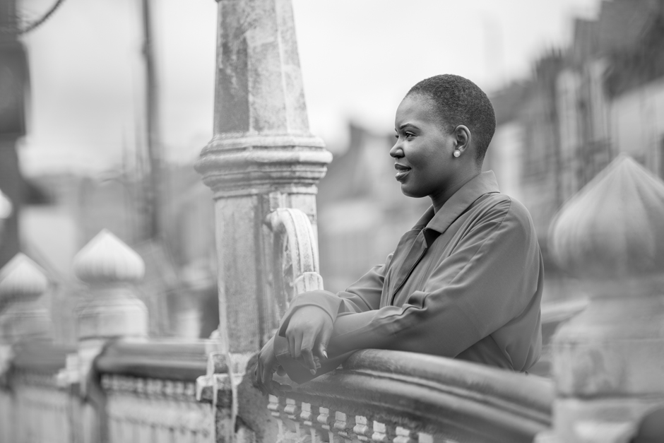 Black businesswoman looking out over Tonbridge highstreet bridge captured by Kent photographer Victoria Green
