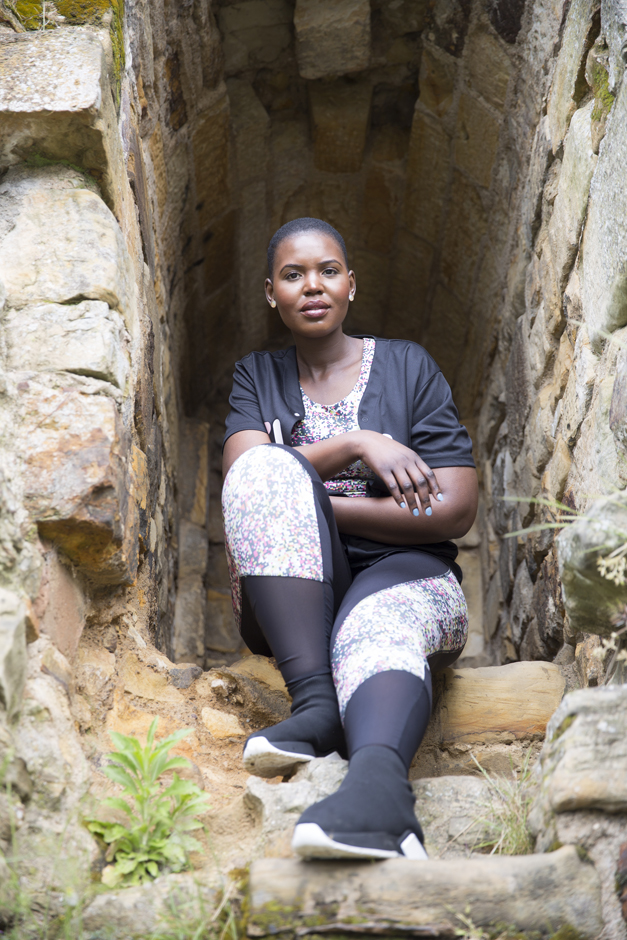 Black woman portrait sitting at top of rocks captured by Kent photographer Victoria Green