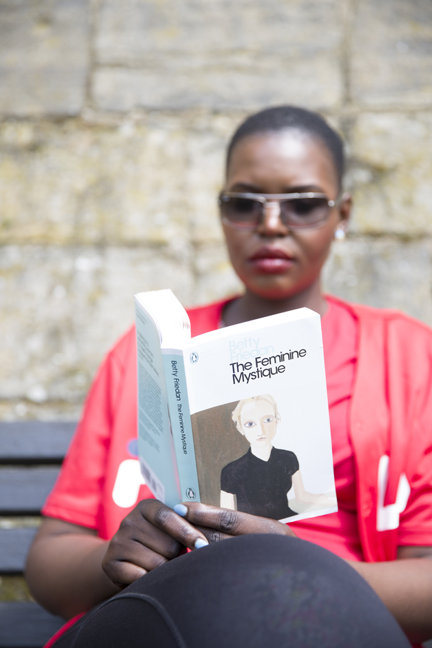 Black woman reading a life coaching book 'The Feminine Mystique' by Betty Friedan, captured by Kent photographer Victoria Green