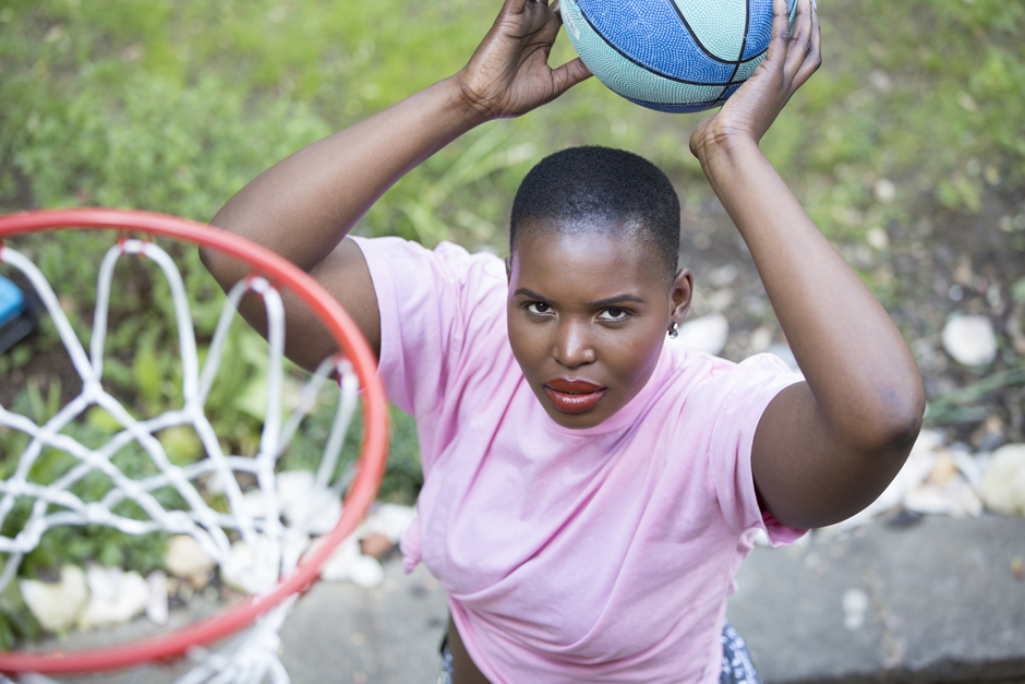Black woman holding basketball ready to shoot in the hoop captured by Kent photographer Victoria Green