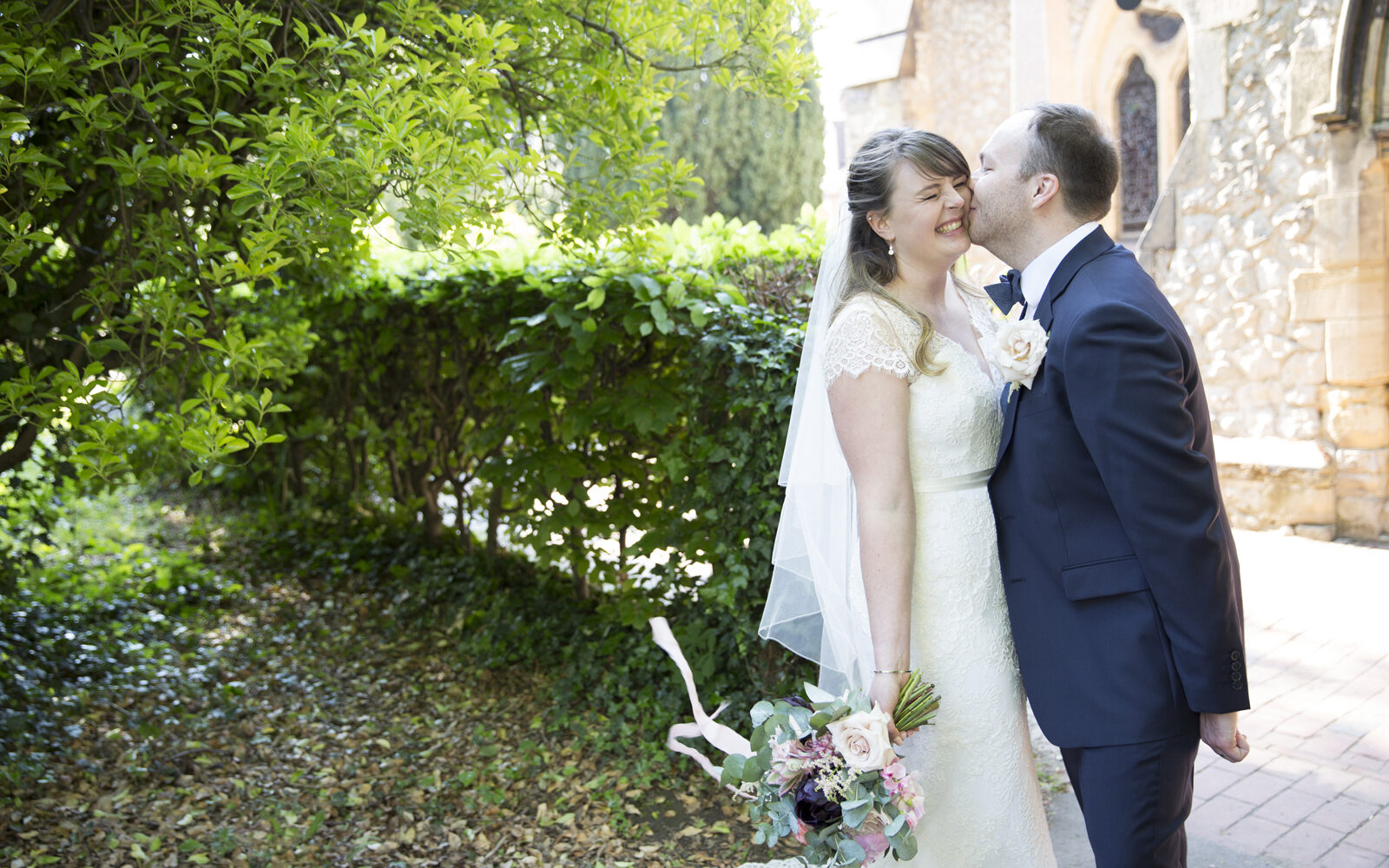 Bride and groom sharing a kiss outside St Stephen's Church in Tonbridge, Kent. Captured by Tonbridge wedding photographer Victoria Green.