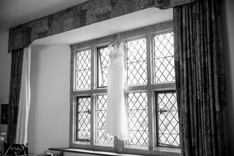 Wedding dress hanging up at window at Nettlestead Place in Maidstone Kent. Captured by Kent wedding photographer, Victoria Green