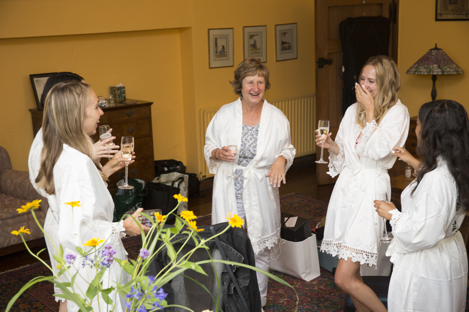 Bride's mum and bridesmaids laughing holding a glass of champagne in the Nettlestead Place bridal suite. Captured by Kent wedding photographer, Victoria Green.