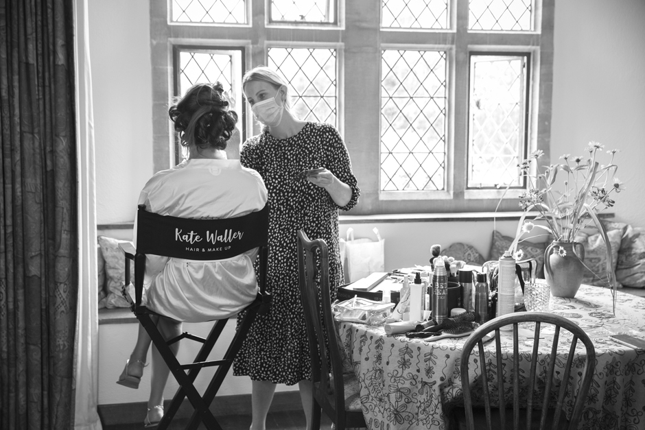 Back of bride sitting in make-up chair having her make-up done by Kate Waller wearing a face mask. Captured by Kent wedding photographer, Victoria Green.