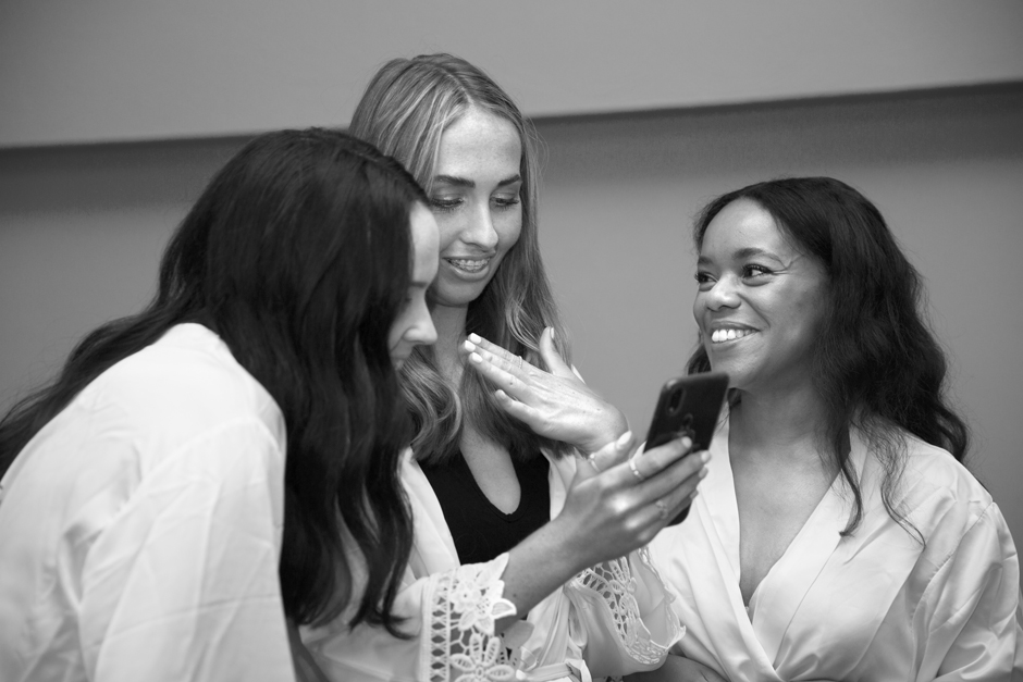 Bridesmaids laughing looking at a phone at Nettlestead Place, Maidstone in Kent.