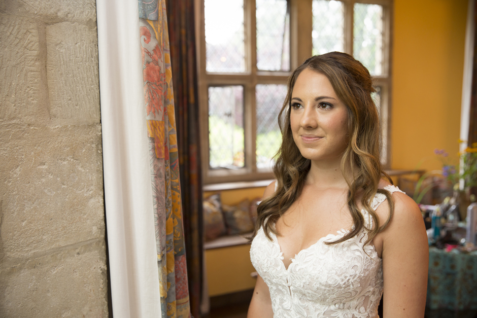 Bride looking thoughtfully outside of window in the bridal suite at Nettlestead Place. Captured by Kent wedding photographer Victoria Green.