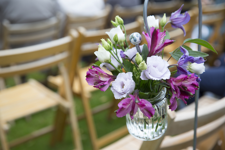 Fresh purple and pink flowers in hanging jam jar at Nettlestead Place outside wedding ceremony. Captured by Kent wedding photographer Victoria Green.