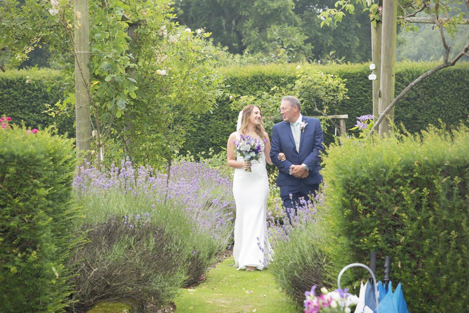 Bride and bride's dad walking down the aisle at outside wedding ceremony at Nettlestead Place. Captured by Kent wedding photographer, Victoria Green.