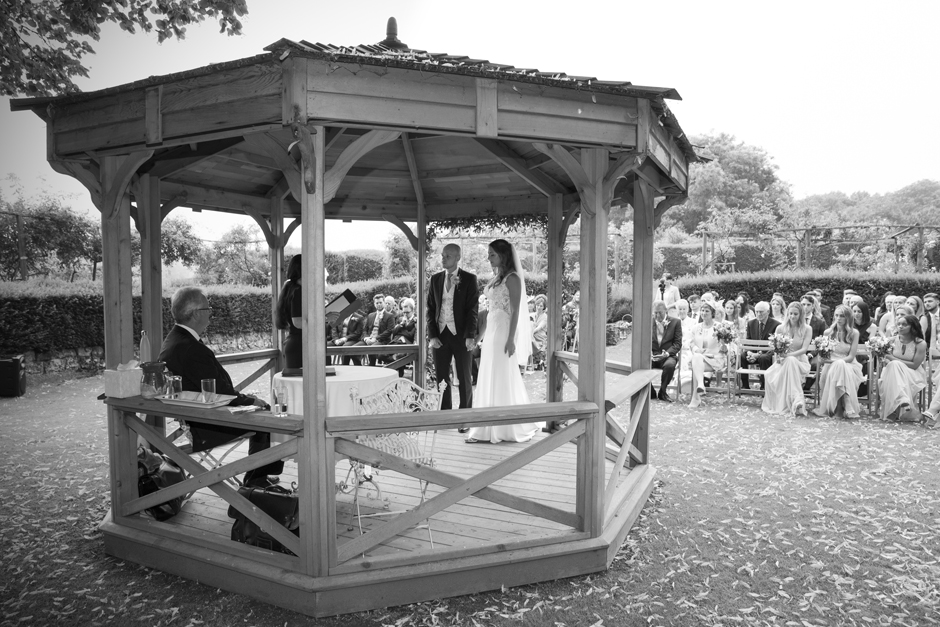 Front of wooden gazebo with guests behind and bride and groom standing under. Captured at Nettlestead Place by Victoria Green Photography.