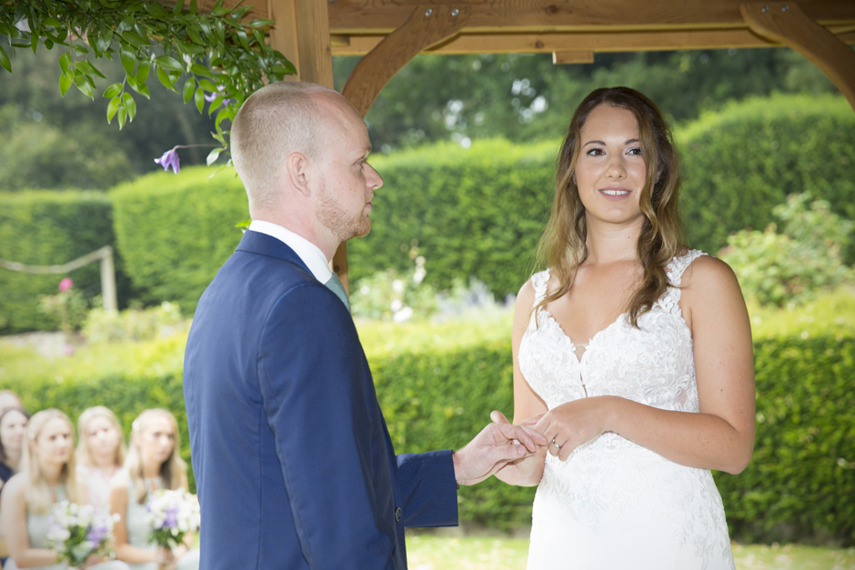 Close-up of bride and groom in outside wedding ceremony at Nettlestead Place. Bride holding groom's hand saying vows. Captured by photographer Victoria Green.