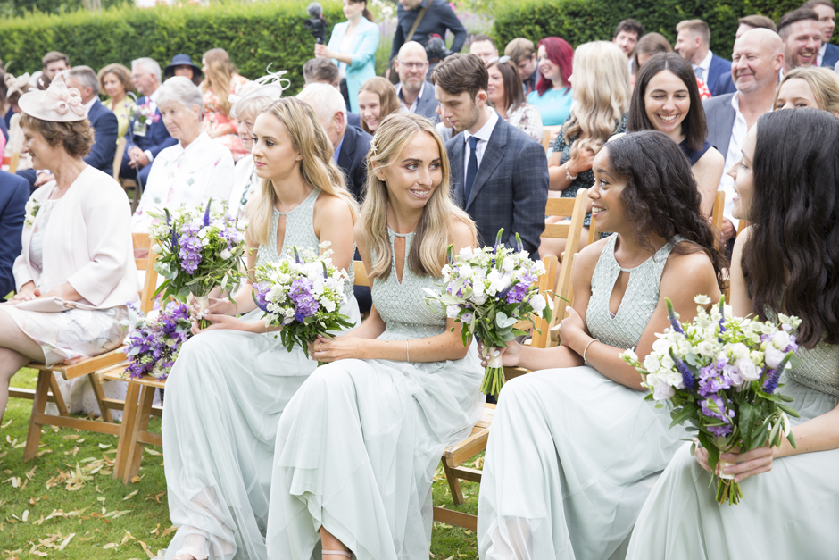 Bridesmaids laughing in outside ceremony at Nettlestead Place, Maidstone in Kent.