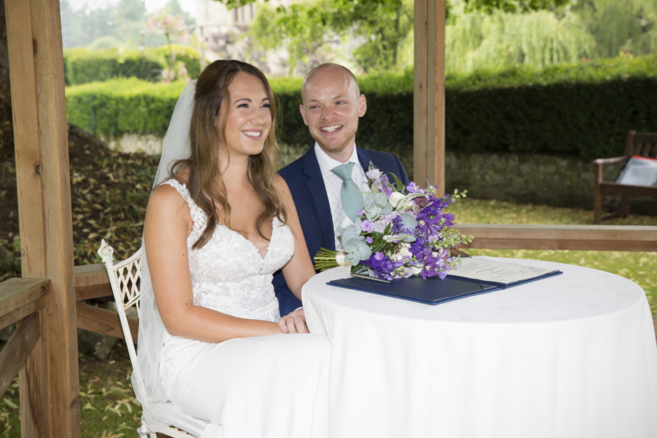 Bride and groom laughing at table signing the register at outside wedding ceremony at Nettlestead Place in Kent. Captured by Kent wedding photographer, Victoria Green.