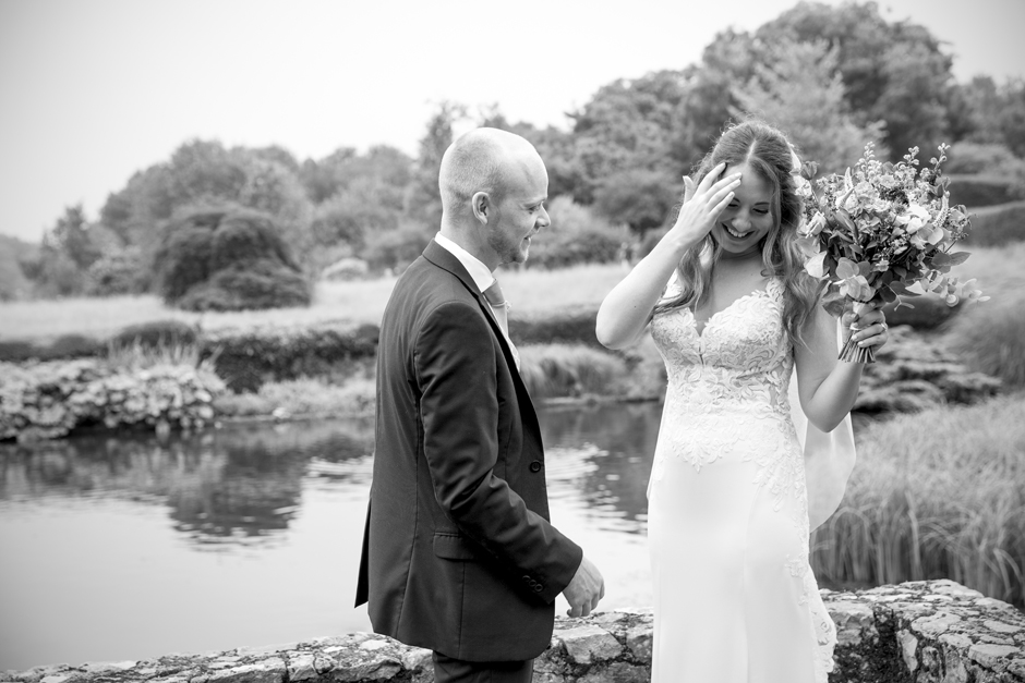 Bride and Groom laughing at Nettlestead Place wedding, standing by the lake, Captured by Kent wedding photographer, Victoria Green.