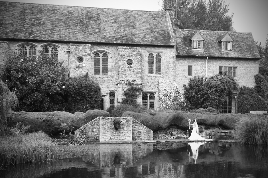 Bride and groom walking by lake at Nettlestead Place in Maidstone, Kent. Captured by wedding photographer, Victoria Green.