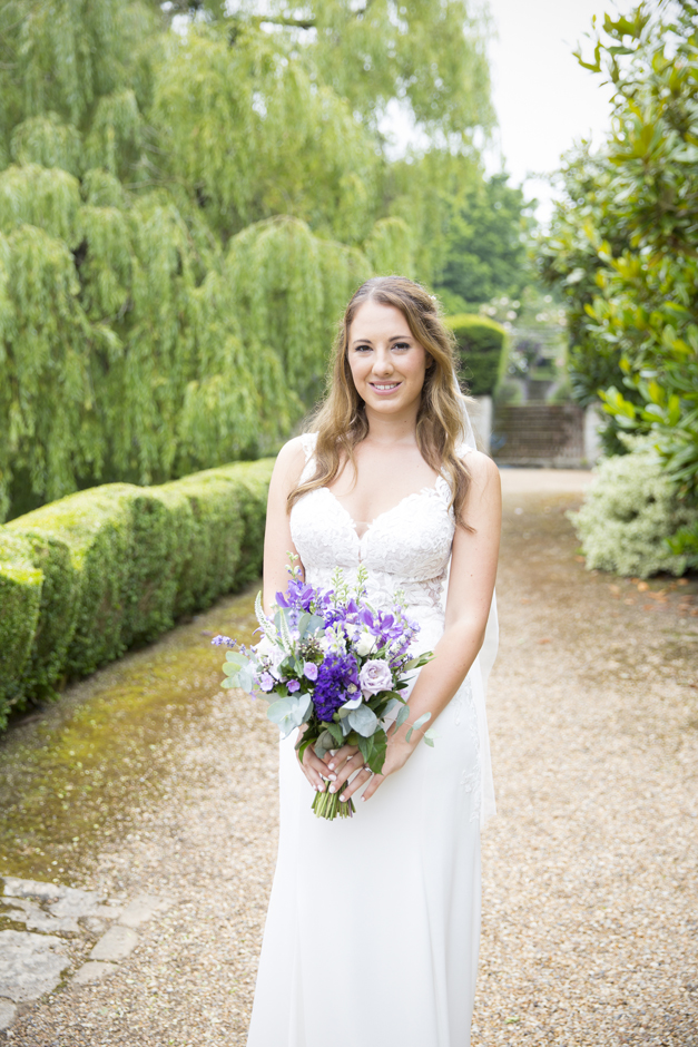 Bride portrait standing holding purple fresh bouquet at Nettlestead Place wedding. Captured by Kent wedding photographer, Victoria Green.