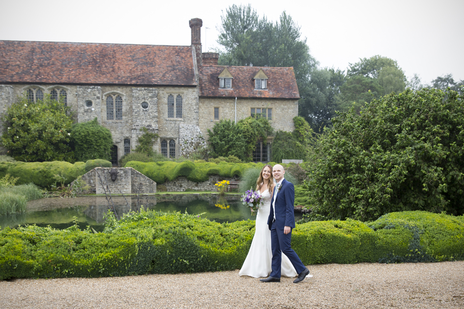 Bride and groom walking together at Nettlestead Place with house and lake in the background. Captured by Kent wedding photographer, Victoria Green.