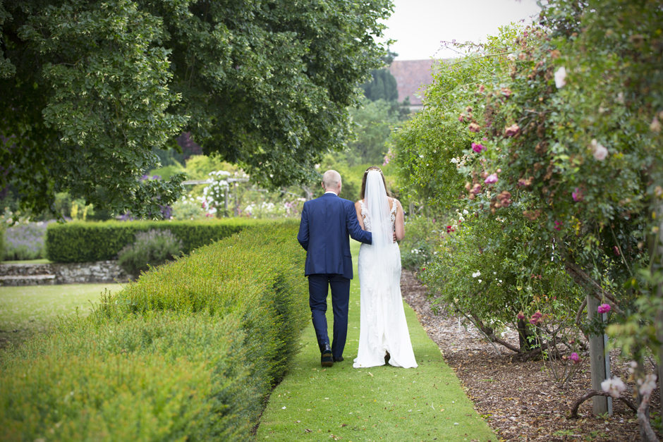 Back of wedding couple as they walk through the rose gardens at Nettlestead Place, Maidstone in Kent. Captured by wedding photographer, Victoria Green.