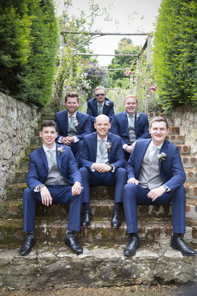 Groom and groomsmen sitting on steps at Nettlestead Place wedding in Maidstone, Kent. Captured by photographer Victoria Green.