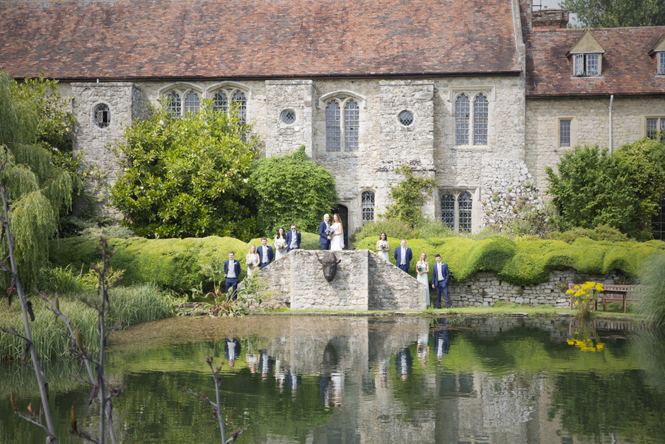 Bride and groom with bridesmaids and groomsmen on steps by lake at Nettlestead Place wedding.