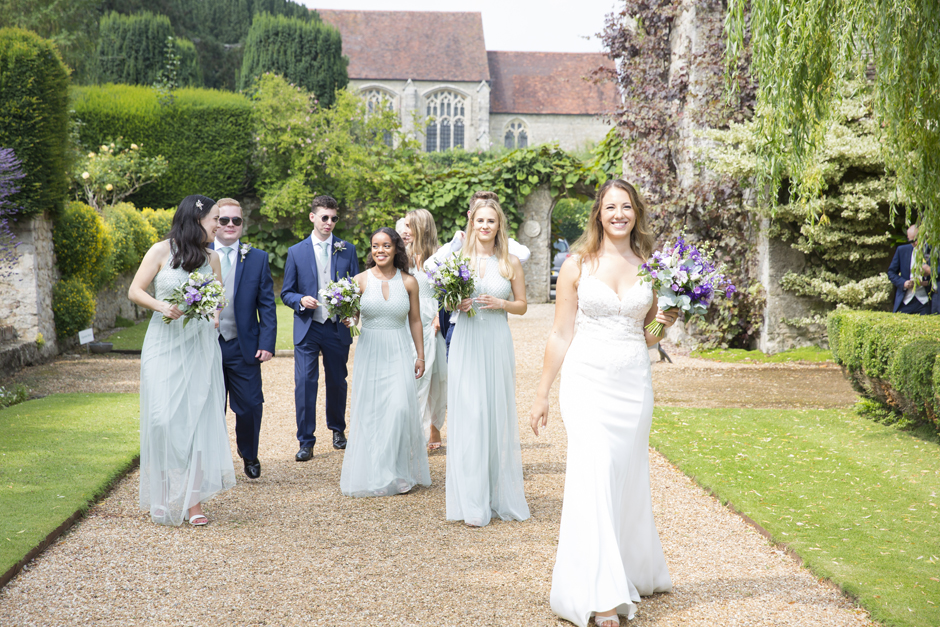 Bride and bridesmaids and groomsmen laughing walking in the grounds at Nettlestead Place. Captured by wedding photographer, Victoria Green.