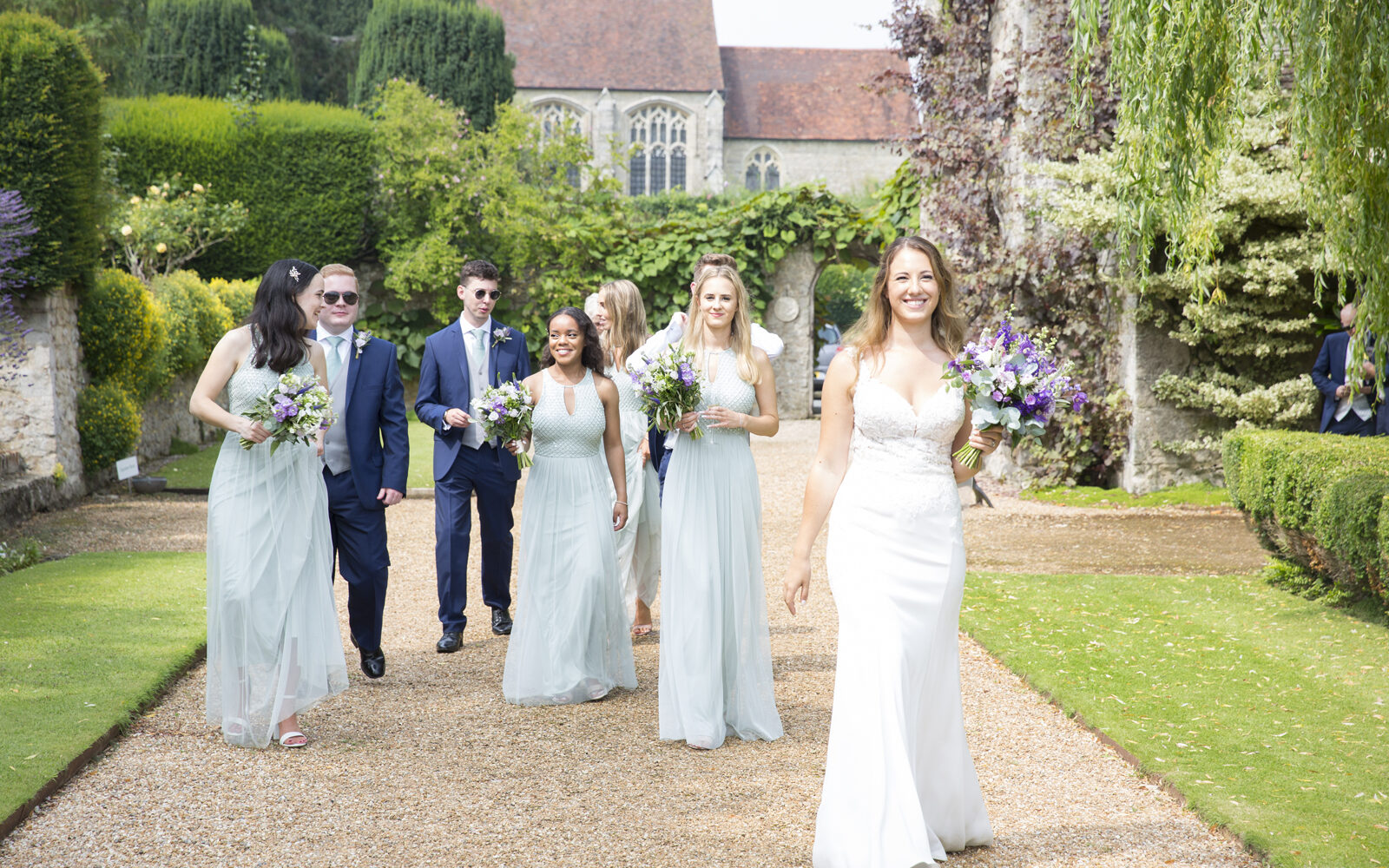 bride with bridal party walking around the grounds at Nettlestead Park in Maidstone. Captured by Kent wedding photographer, Victoria Green.