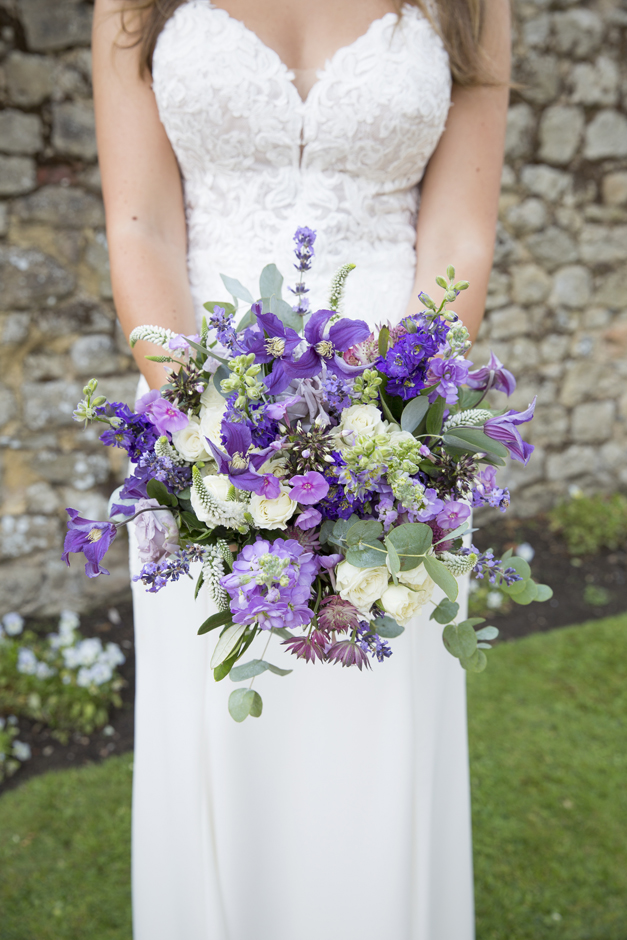 Bride with fresh purple bouquet at Nettlestead Place wedding in Maidstone, Kent.