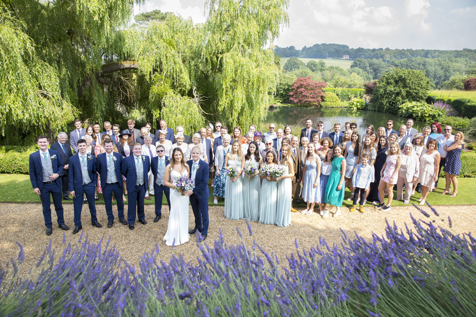 All group portrait of all family and friends with bride and groom captured at Nettlestead Place in Maidstone, Kent by photographer Victoria Green.