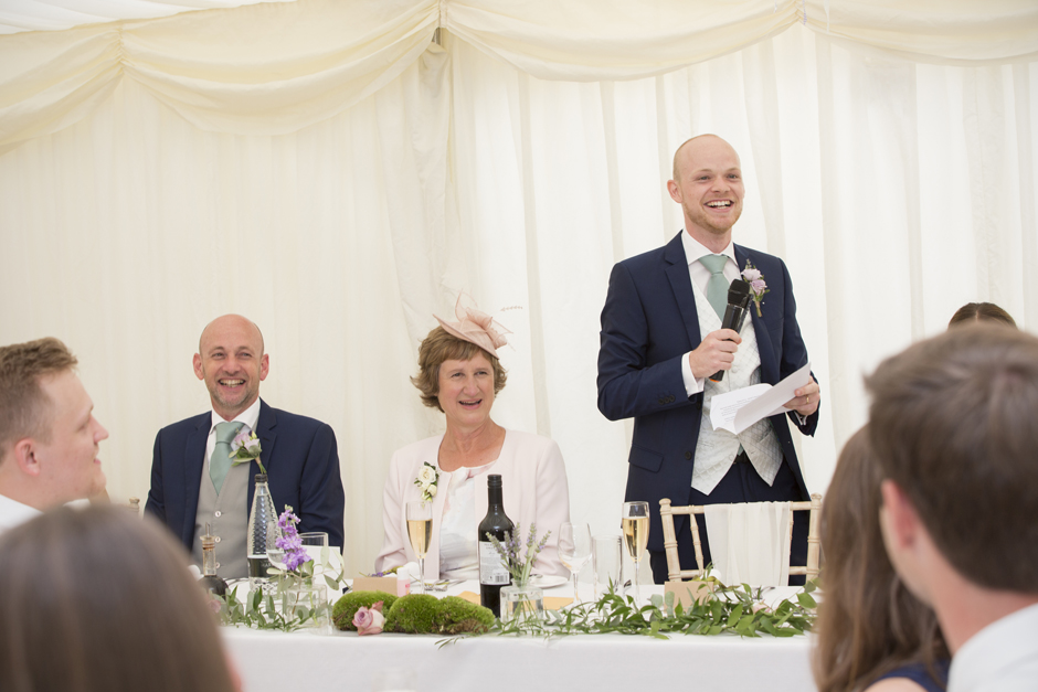 Groom saying speech while parents laugh to his side - captured at Nettlestead Place in Maidstone, Kent.