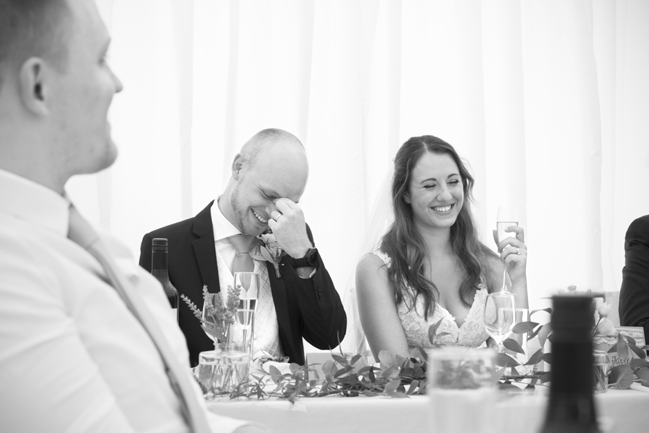 Bride and groom laughing at Nettlestead Place in Maidstone in Kent. Groom looking embarrassed!