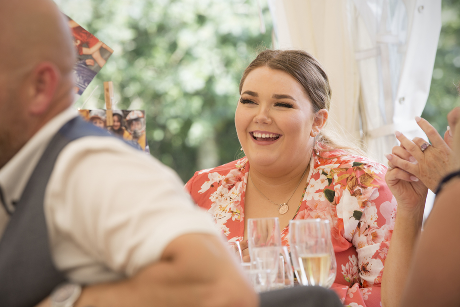 Female wedding guest laughing during speeches at Nettlestead Place in Maidstone, Kent.