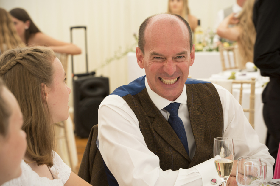 Male wedding guest with very big grin to camera during speeches at Nettlestead Place wedding in Maidstone, Kent.
