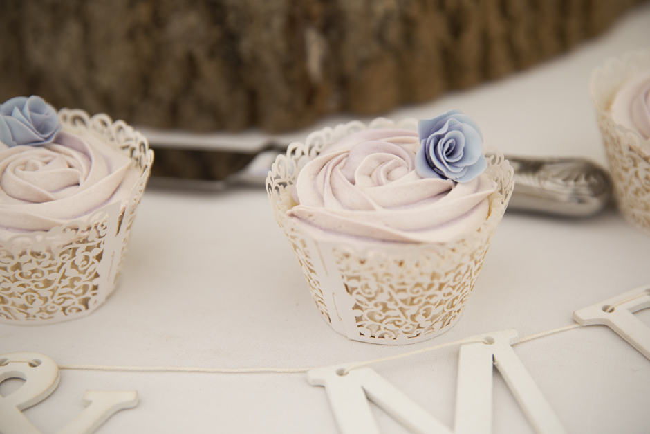 Lilac cupcake with tiny blue rose on top at Nettlestead Place wedding in Maidstone, Kent.