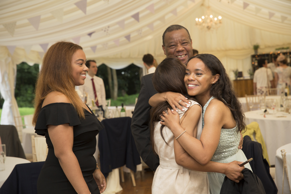 Evening wedding guests hug bridesmaid at reception at Nettlestead Place, Kent.