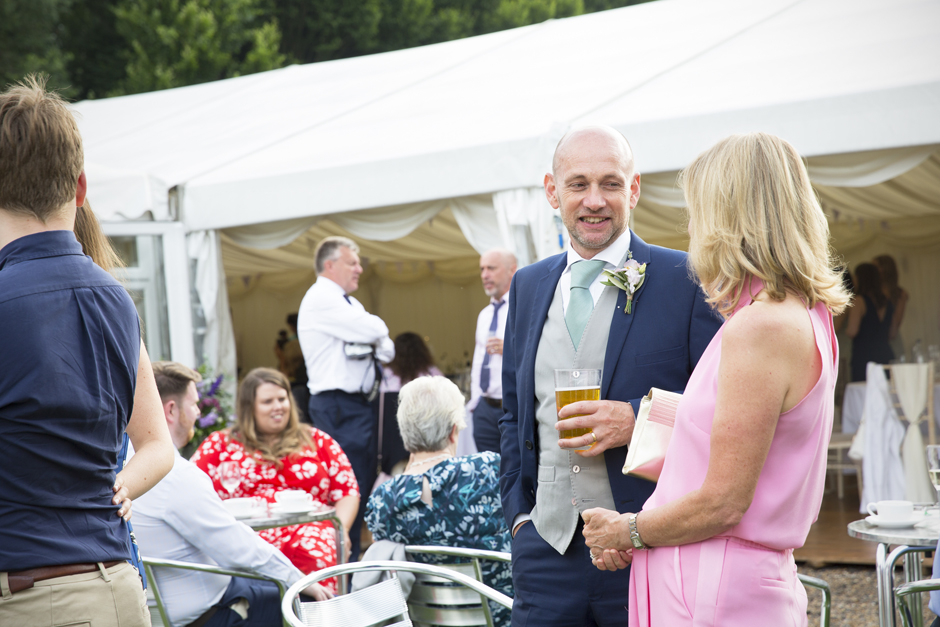 Groom's father having a beer with wedding guest outside the marquee at Nettlestead Place in Kent.