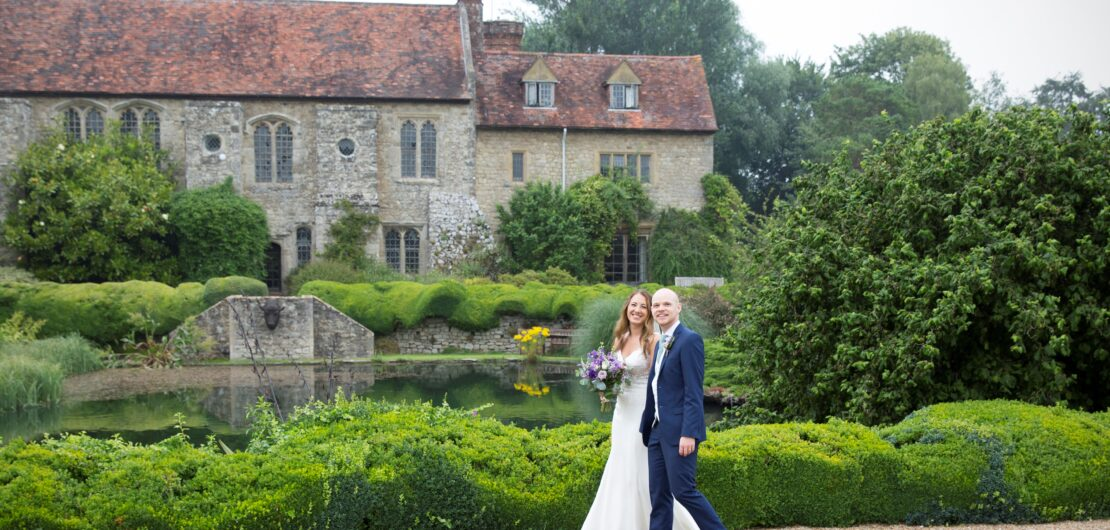 bride and groom walking in front of Nettlestead Place in Kent, captured by Kent wedding photographer Victoria Green