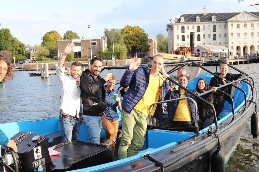 A group of people in a small boat in a body of water  Description automatically generated