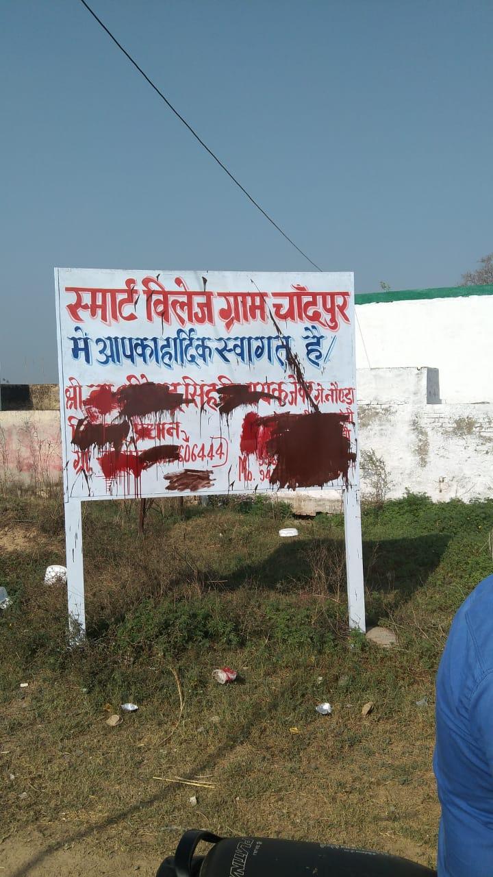 विधायक का नाम लिखे बोर्ड की पुताई से ग्रामीणों में आक्रोश