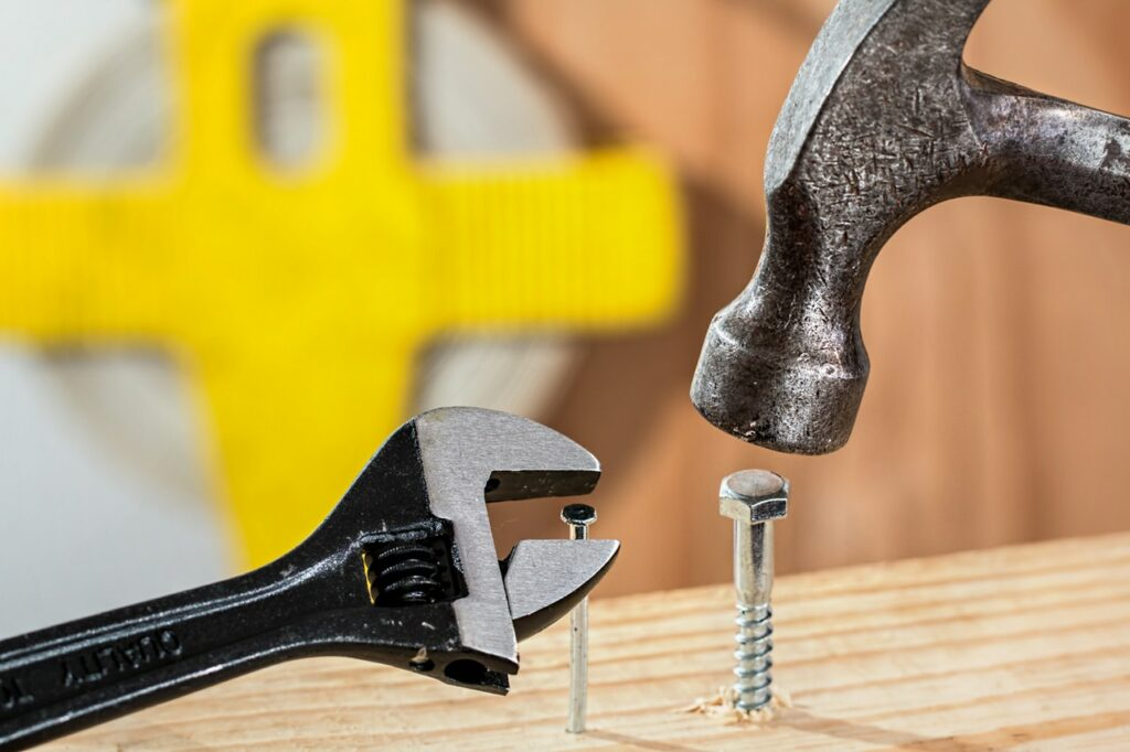 Someone hammering a screw. This represents good tools being misused, which is what happens with Goal Setting Mistakes