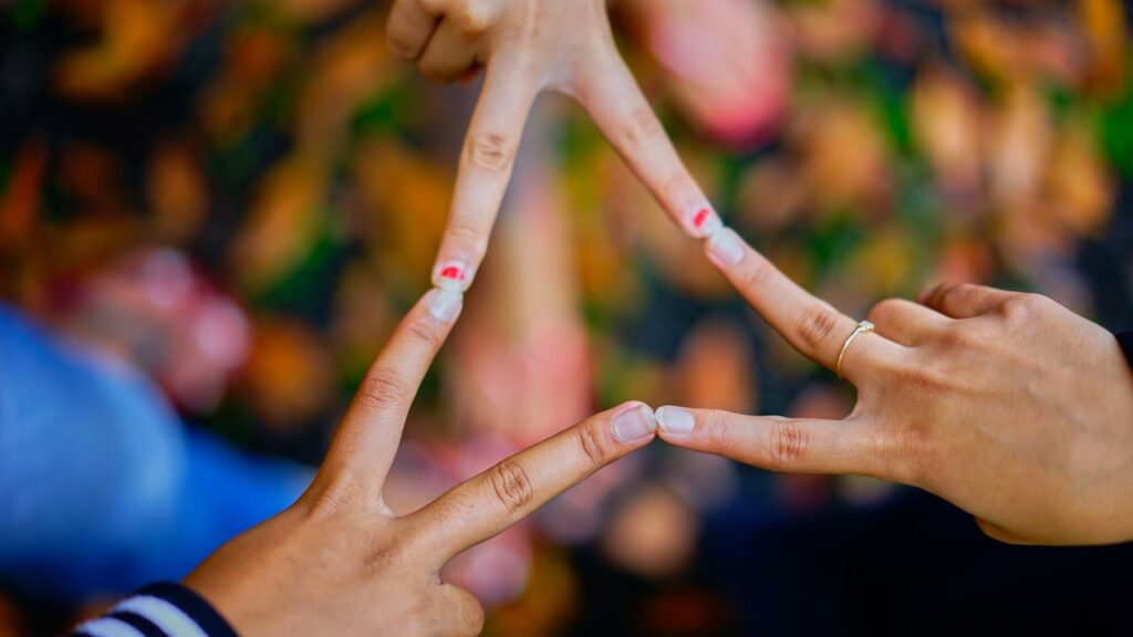 """People pressing fingers together demonstrating the """"connected"""" part of Blanchard's ABCDs of trust"""