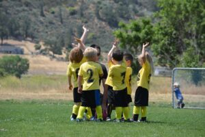 A team of toddlers hi-fiving, perhaps Huddles or Stand-up Meetings help them