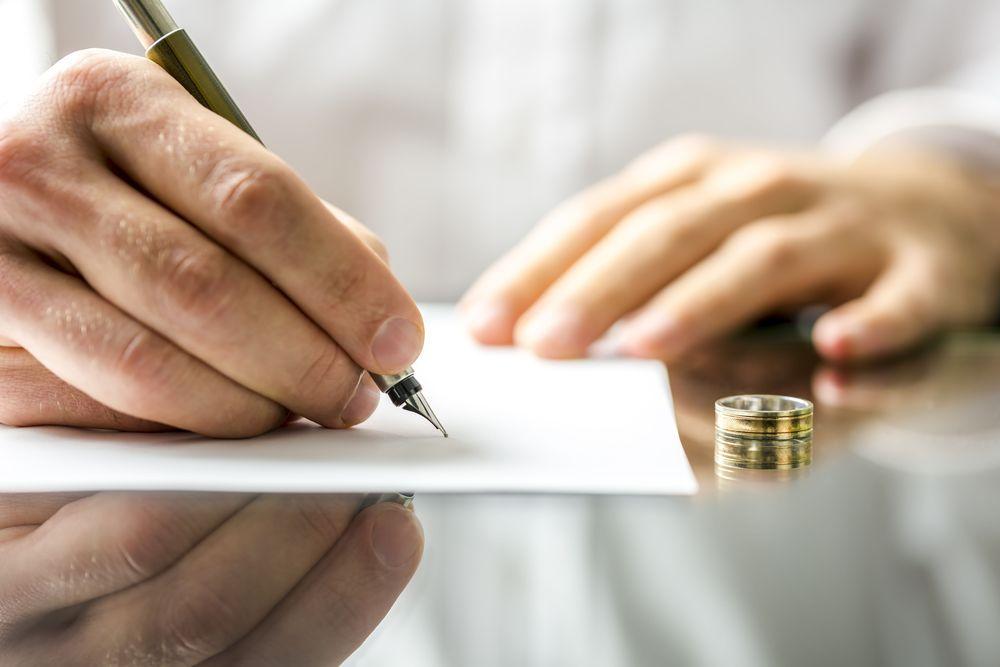 A closeup shot of a person signing a paper