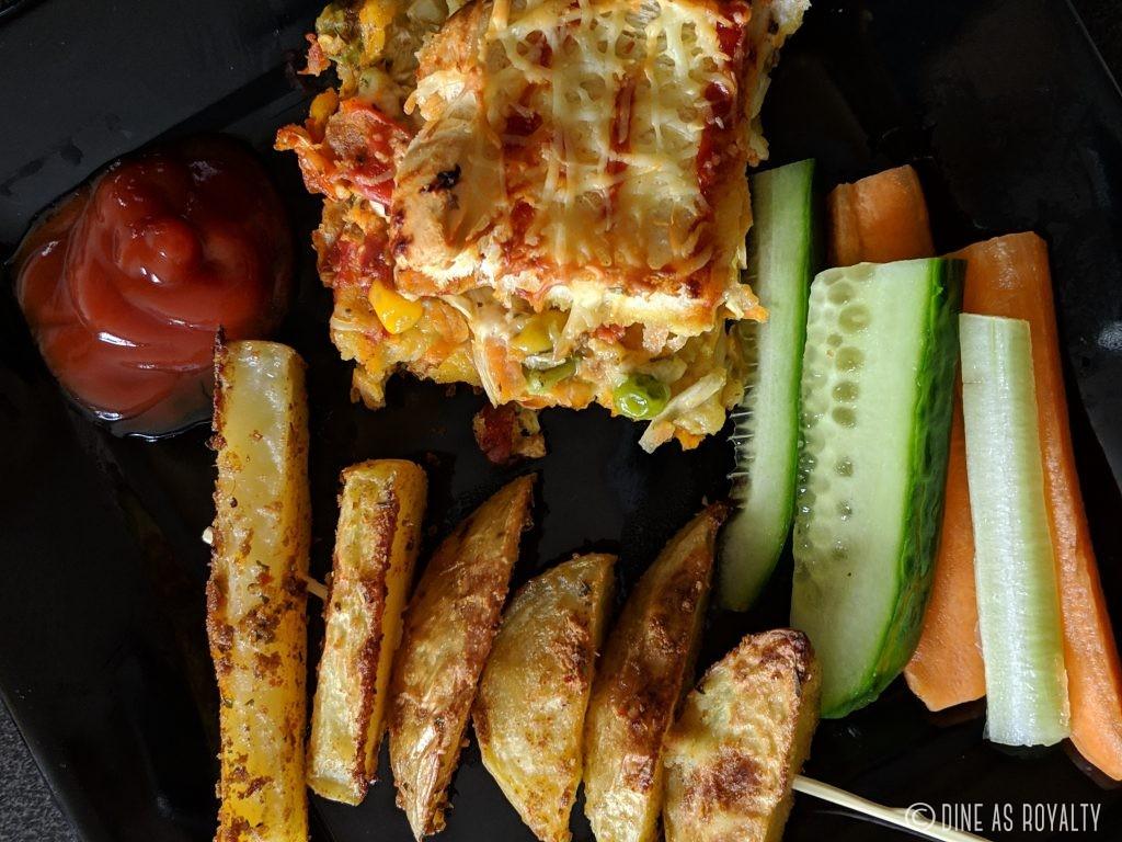 Yaji potatoes with ketchup, a slice of ajekusine casserole and fresh veggies.